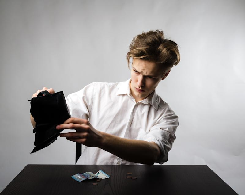 Worried young man in white is looking at an empty wallet.
