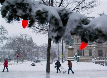 People make their way down a snow-covered street, as a winter storm moves across the midwest, in Milwaukee, Wisconsin December, 22, 2013. REUTERS/Darren Hauck