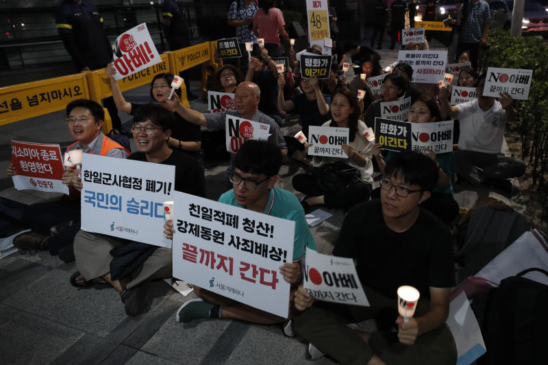 """South Korean protesters react during a rally about the General Security of Military Information Agreement, or GSOMIA, in front of Japanese embassy in Seoul, South Korea, Thursday, Aug. 22, 2019. South Korea said Thursday it will terminate an intelligence-sharing deal with Japan that focused on classified information about North Korea, a surprise announcement that is likely to set back U.S. efforts to bolster security cooperation with two of its most important allies in the Asian region. The sign read """"No Abe."""" and """"Welcome, termination of GSOMIA."""" and """"The scrapping of the South Korea-Japan deal is a people's victory."""" (AP Photo/Lee Jin-man)"""