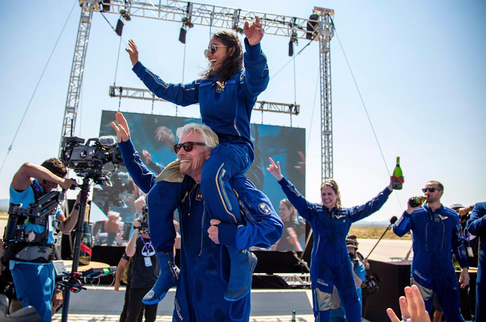 Virgin Galactic founder Sir Richard Branson carries crew member Sirisha Bandla on his shoulders while celebrating their flight to space at Spaceport America in New Mexico (AP)
