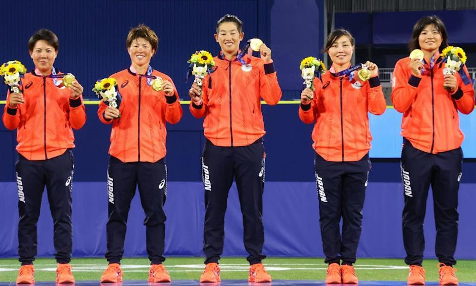 Japan's softball players stand with their gold medals on the podium.