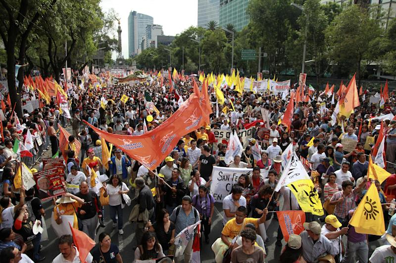 Thousands of supporters of Andres Manuel Lopez Obrador, presidential candidate for the Democratic Revolution Party (PRD) walk towards the main Zocalo plaza to participate in Lopez Obrador's final campaign closing rally in Mexico City, Mexico, Wednesday, June 27, 2012. Next July 1, Mexico will hold presidential elections. (AP Photo/Dario Lopez-Mills)