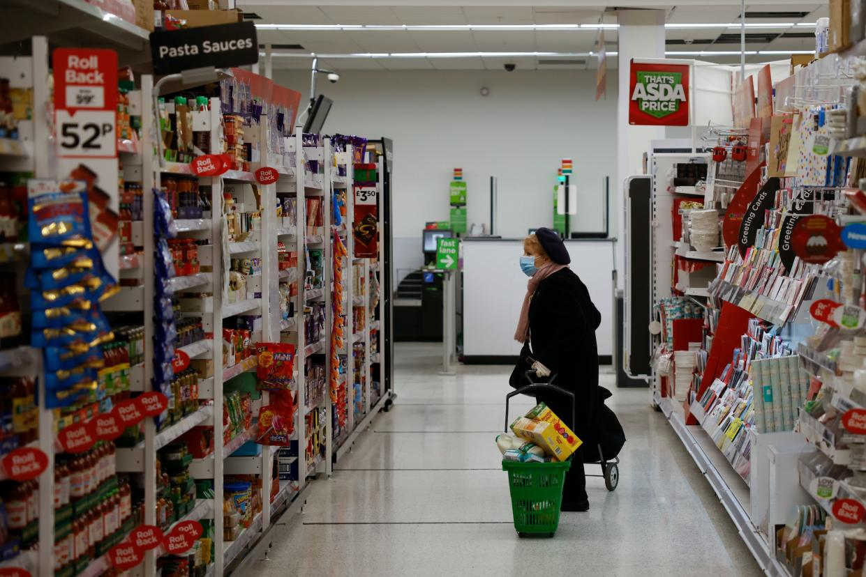 An elderly shopper wearing a face mask or covering due to the COVID-19 pandemic, pulls a shopping basket inside an ASDA supermarket in Walthamstow in north east London on December 22, 2020.. - The British government said Tuesday it was considering tests for truckers as part of talks with French authorities to allow the resumption of freight traffic suspended due to a new strain of coronavirus. Britain was plunged into fresh crisis last week with the emergence of a fresh strain of the virus, which is believed to be up to 70 percent more transmissible than other forms. (Photo by Tolga Akmen / AFP) (Photo by TOLGA AKMEN/AFP via Getty Images)