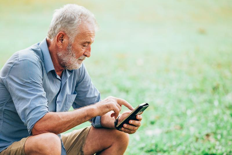 Older man sitting outdoors while typing on a smartphone.