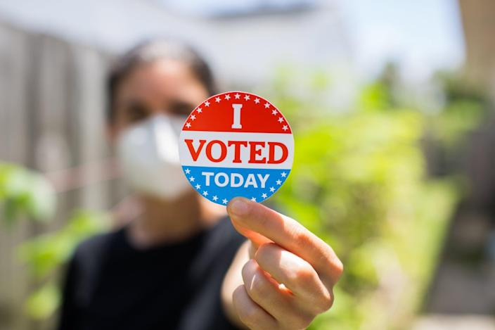Young woman wearing face mask holding I voted today sticker.