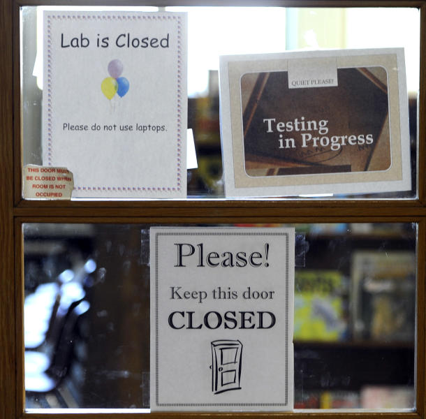 FILE - In this May 1, 2013, file photo signs are posted on a closed classroom door, indicating that testing is going on inside, at an elementary school in Mishawaka, Ind. A new poll from the Associated Press-NORC Center for Public Affairs Research finds parents of school-age children view standardized tests as a useful way to track student progress and school quality. Most parents say their own children are given about the right number of standardized tests, according to the AP-NORC poll. And almost three quarters say they favor changes that would make it easier for schools to fire poorly performing teachers. (AP Photo/Joe Raymond, File)