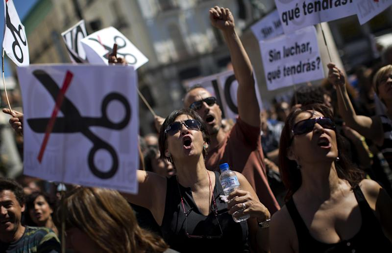 Civil servants shouts slogans condemning the recent austerity measures announced by the Spanish government, during a demonstrations in Madrid, Spain, on Friday July 13, 2012. Spanish civil servants, some dressed in the black of mourning, took to the streets Friday to protest their second wave of wage cuts in as many years as the government prepared to approve austerity measures that include those reductions as part of a deficit-cutting plan to save euro 65 billion through 2015. (AP Photo/Emilio Morenatti)