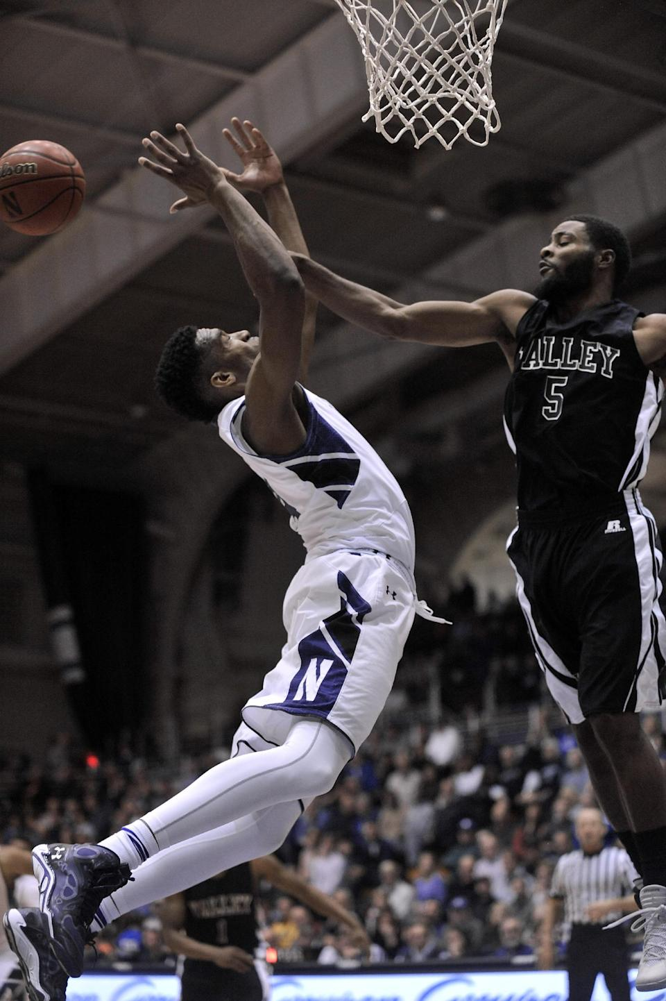 Northwestern's Vic Law (4) goes up for a rebound against Mississippi Valley State's Jeffery Simmons (5) during the first half of an NCAA college basketball game in Evanston, Ill., Sunday, Dec. 14, 2014. (AP Photo/Paul Beaty)