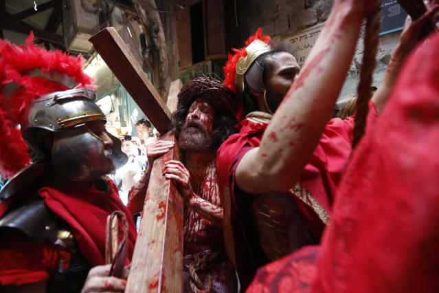 An actor dressed as Jesus Christ carries a cross as he reenacts the crucifixion walk along the Via Dolorosa towards the Church of the Holy Sepulchre, traditionally believed by many to be the site of the crucifixion of Jesus Christ, during the Good Friday procession in Jerusalem's old city, Friday, April 19, 2019. (AP Photo/Ariel Schalit)
