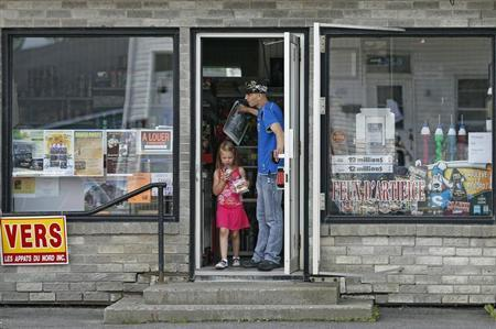 A resident and his child walk out of a convenience store, in a part of the town that has been reopened today, in Lac Megantic
