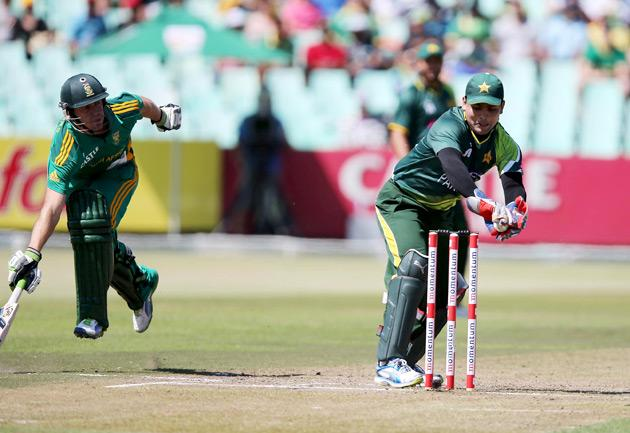 Kamran Akmal (R) of Pakistan tries unsuccessfully to run out Farhaan Behardien of South Africa (L)  during the 4th Momentum ODI match at Sahara Stadium Kingsmead on March 21, 2013 in Durban.  AFP PHOTO  / STR        (Photo credit should read STR/AFP/Getty Images)