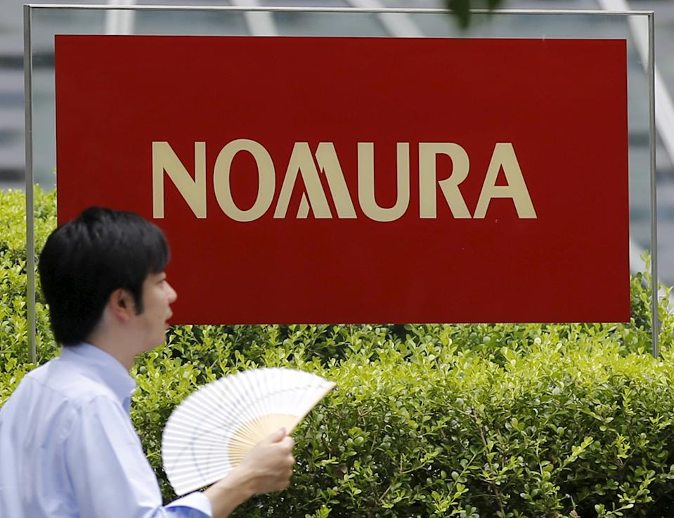 A man walks past a sign of Nomura Holdings in Tokyo July 29, 2015. Japanese brokerage Nomura Holdings's quarterly net profit more than tripled as strong demand from customers to trade domestic stocks boosted its retail revenue. REUTERS/Toru Hanai