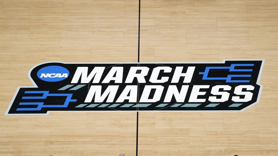 The March Madness logo is shown on the court during the first half of a men's college basketball game in the first round of the NCAA tournament at Bankers Life Fieldhouse in Indianapolis, Saturday, March 20, 2021. The Associated Press has learned that the NCAA has not tested players for performance-enhancing drugs while they've been at March Madness and other recent college championships. Three people familiar with testing protocols tell AP full-scale testing has not resumed since the coronavirus pandemic shut down college sports a year ago. (AP Photo/Paul Sancya)