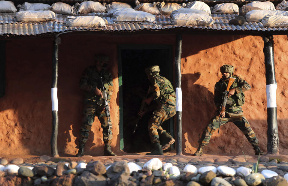 Indian army soldiers display a cordon and search operation (CASO) during a training session at a corps battle school at Sarol in Rajouri, about 135 kilometers (84 miles) northwest of Jammu, India, Tuesday, Dec. 15, 2020. AP journalists were recently allowed to cover Indian army counterinsurgency drills in Poonch and Rajouri districts along the Line of Control. The training focused on tactical exercises, battle drills, firing practice, counterinsurgency operations and acclimatization of soldiers to the harsh weather conditions. (AP Photo/Channi Anand)