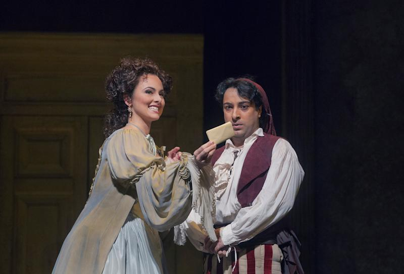 """In this Dec. 14, 2012 publicity photo, Isabel Leonard, left, as Rosina and Rodion Pogossov, as Figaro, are seen in Rossini's """"The Barber of Seville,"""" during rehearsal at the Metropolitan Opera in New York. (AP Photo/Metropolitan Opera, Ken Howard)"""