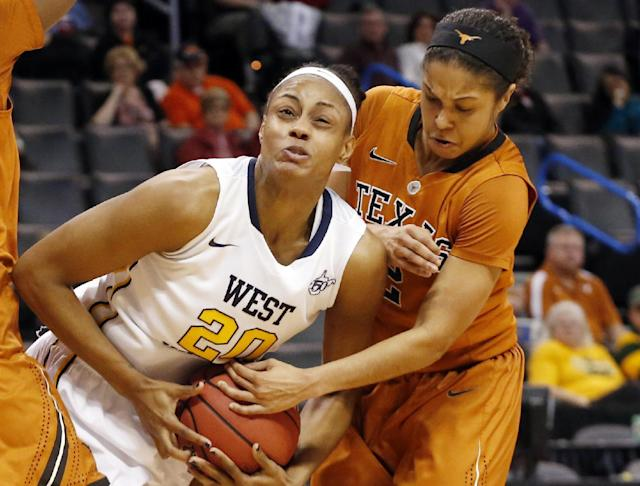 Texas guard Celina Rodrigo, right, reaches in to try and take the ball away from West Virginia center Asya Bussie (20) in the first half of an NCAA college basketball game in the semifinals of the Big 12 Conference women's college tournament in Oklahoma City, Sunday, March 9, 2014. (AP Photo/Sue Ogrocki)