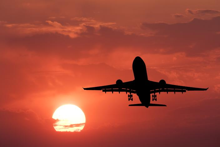 Silhouette of landing aircraft and red sky with sun. Landscape with passenger airplane is flying in the sky with clouds at sunset. Travel background. Passenger airliner. Commercial airplane. Business