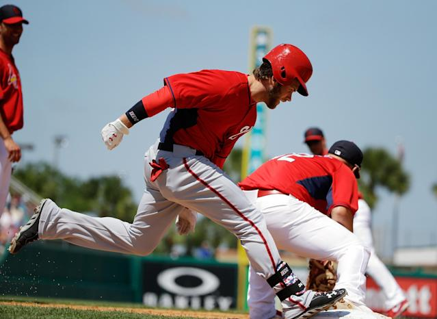 Washington Nationals' Bryce Harper, left, is out at first base as St. Louis Cardinals' Matt Adams, right, catches the throw from teammate Mark Ellis in the fourth inning of an exhibition spring training baseball game, Wednesday, March 26, 2014, in Jupiter, Fla. (AP Photo/David Goldman)