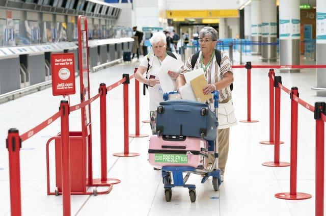 Two women head to a check-in desk at Glasgow Airport