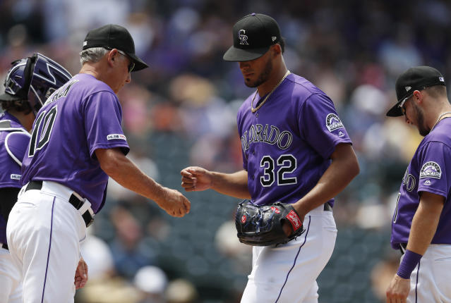 Colorado Rockies manager Bud Black, left, takes the ball from relief pitcher Jesus Tinoco who is pulled from the mound after giving up an RBI-double to San Francisco Giants' Kevin Pillar in the sixth inning of a baseball game Monday, July 15, 2019, in Denver.(AP Photo/David Zalubowski)