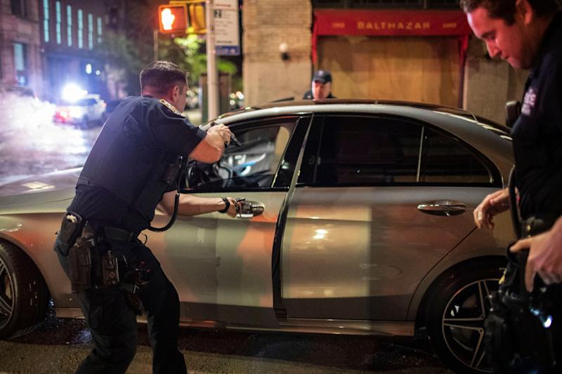 Police stop a driver in the SoHo shopping district Sunday, May 31, 2020, in New York. Protests were held throughout the city over the death of George Floyd, who died May 25 after he was pinned at the neck by a Minneapolis police officer. (AP Photo/Wong Maye-E)