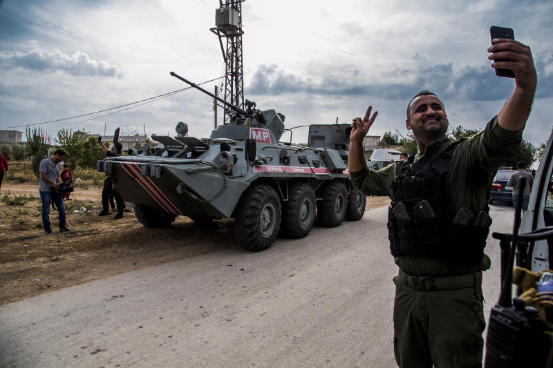 A member of Asayish, or the Internal Security Forces, makes a selfie by an Russian military vehicle during a patrol near Syrian and Turkish border in north Syria, Friday. Oct. 25, 2019. (AP Photo/Baderkhan Ahmad)