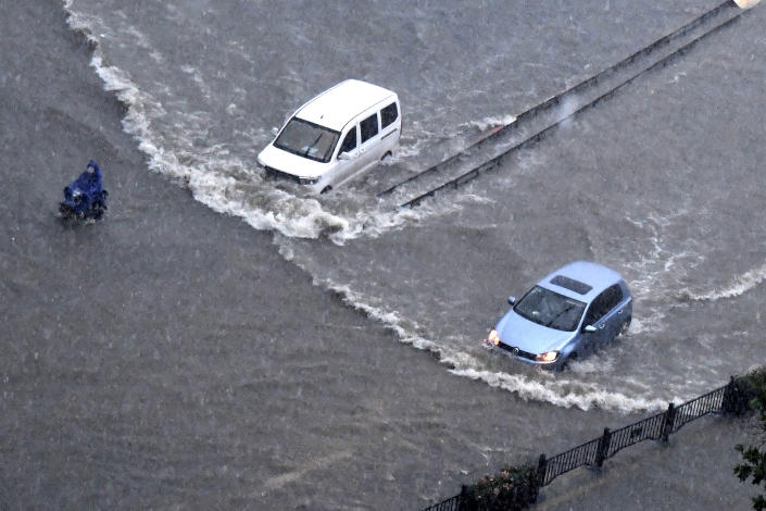 In this photo released by Xinhua News Agency, vehicles pass through floodwaters in Zhengzhou in central China's Henan Province on Tuesday, July 20, 2021. At least a dozen people died in severe flooding Tuesday in a Chinese provincial capital that trapped people in subways and schools, washed away vehicles and stranded people in their workplaces overnight. (Zhu Xiang/Xinhua via AP)