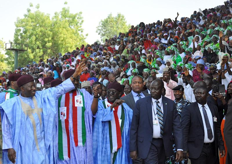 Nigerian President and presidential candidate of the ruling People's Democratic Party (PDP) Goodluck Jonathan (L) waves to supporters during a rally in Maiduguri on January 24, 2015 (AFP Photo/Tunji Omirin)