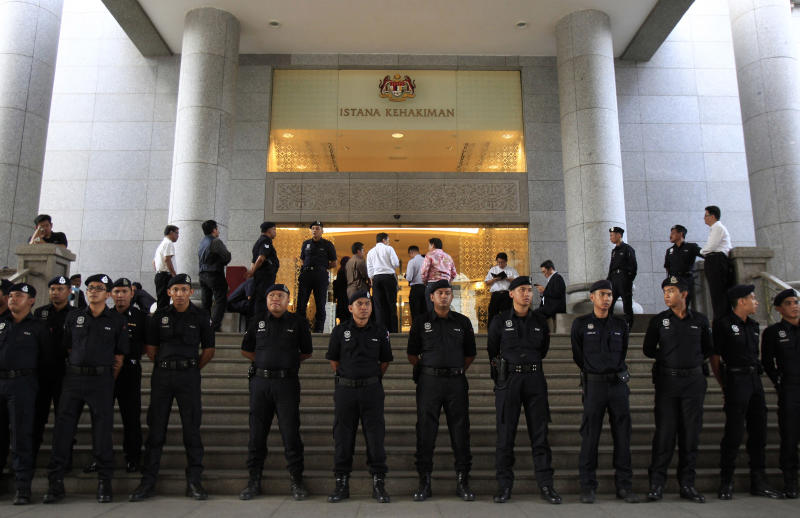 Malaysian police officers stand guard outisde a courthouse in Putrajaya, Malaysia, Friday, March 7, 2014. A Malaysian court Friday found Malaysian opposition leader Anwar Ibrahim guilty on sodomy charges, overturning an earlier acquittal and dealing a major blow to his hopes of contesting a local election this month. (AP Photo/Lai Seng Sin)