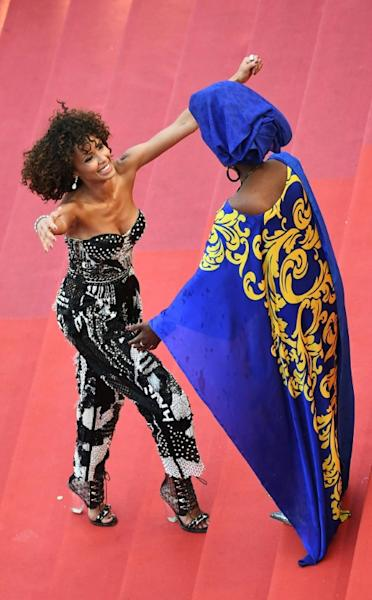French actress and Miss France 2000 Sonia Rolland (l) is welcomed by Burundian singer and member of the Feature Film Jury Khadja Nin as hte protest gets underway