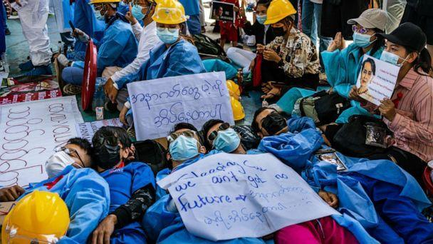 PHOTO: Protesters lies on the ground, Feb. 11, 2021 in Yangon, Myanmar. Myanmar declared martial law in parts of the country as massive protests continued to draw people to the streets a week after the country's military junta staged a coup. (Hkun Lat/Getty Images)