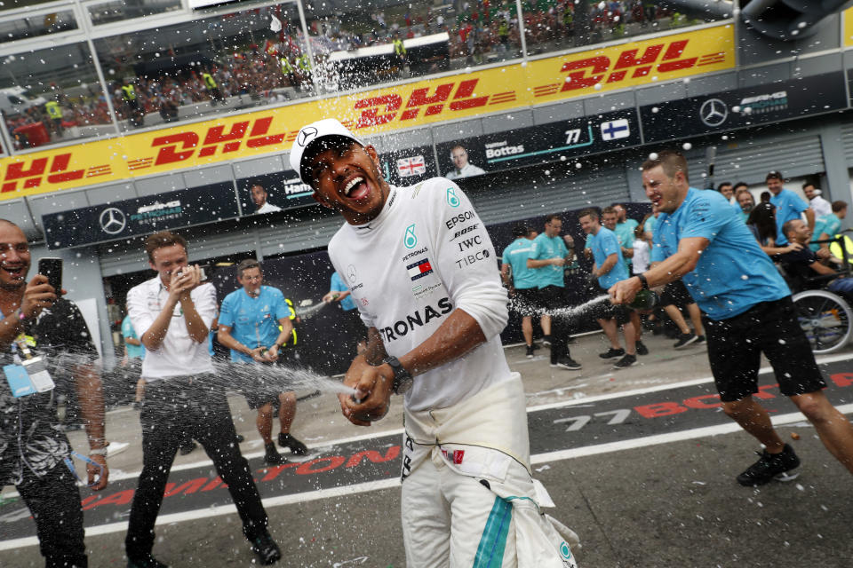 FILE - In this Sunday, Sept. 2, 2018 file photo, Mercedes team members spray champagne at Mercedes driver Lewis Hamilton of Britain celebrating after winning the Formula One Italy Grand Prix at the Monza racetrack, in Monza, Italy. British driver Lewis Hamilton made Formula One history on Sunday, Oct. 25, 2020 winning the Portuguese Grand Prix for a 92nd win to move one ahead of German great Michael Schumacher. (AP Photo/Antonio Calanni, file)