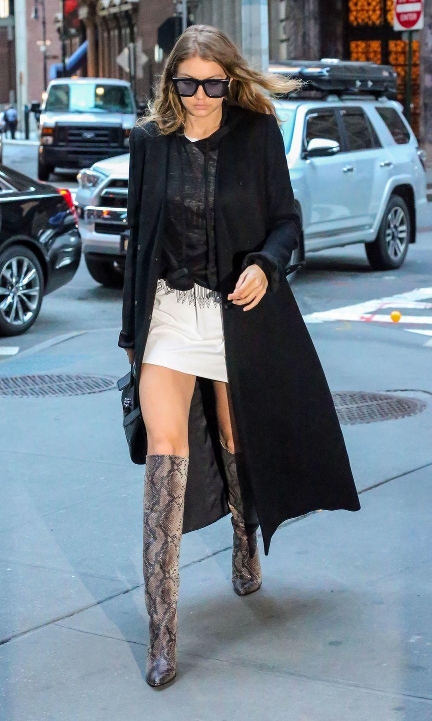 <p>Out in NYC wearing a semi-sheer tee over a mini dress with a black duster jacket and knee-high snakeskin boots. </p>