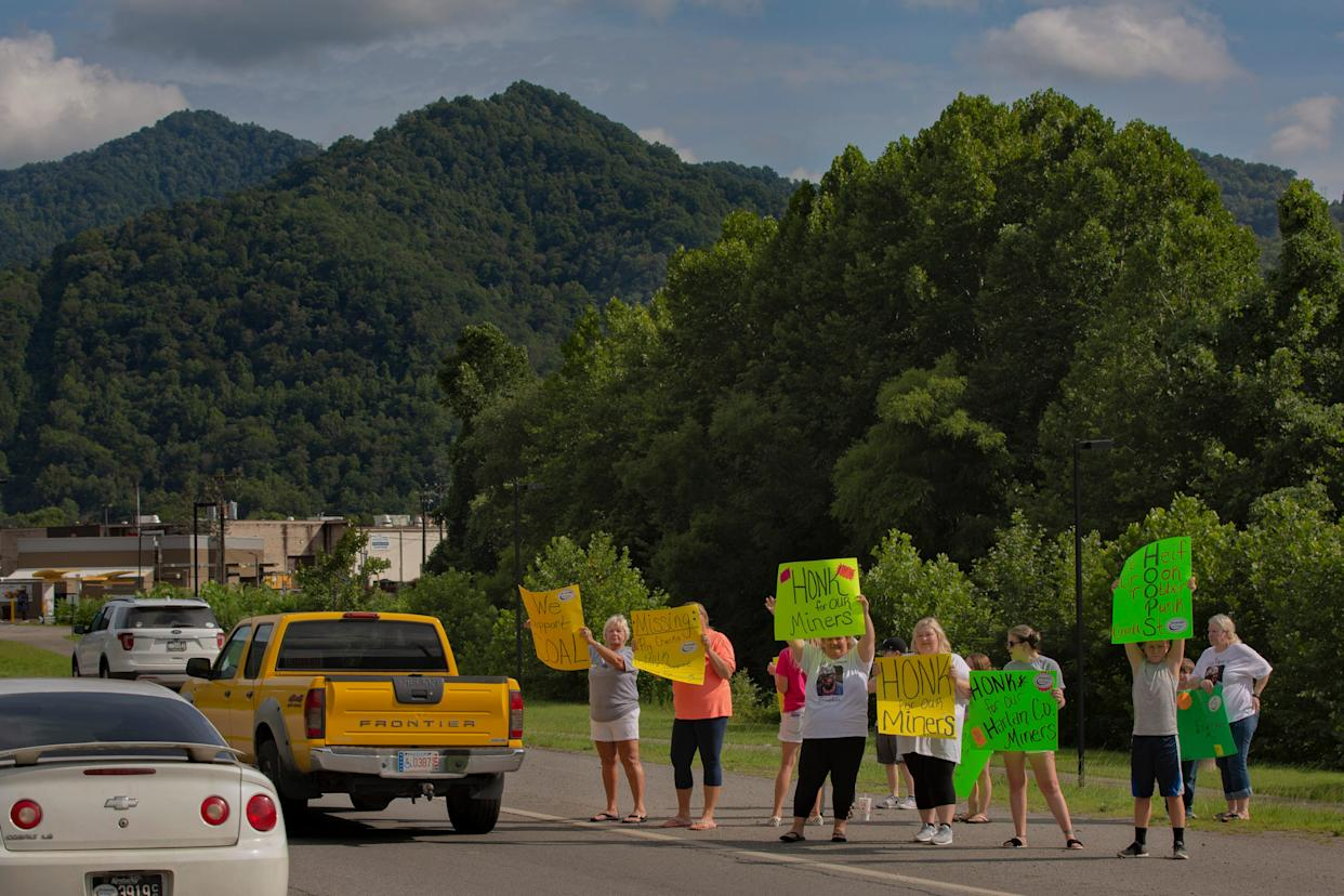 Family members hold signs along Highway 421 in Harlan in support of coal miners affected by the bankruptcy of the Blackjewel coal company. July 18, 2019