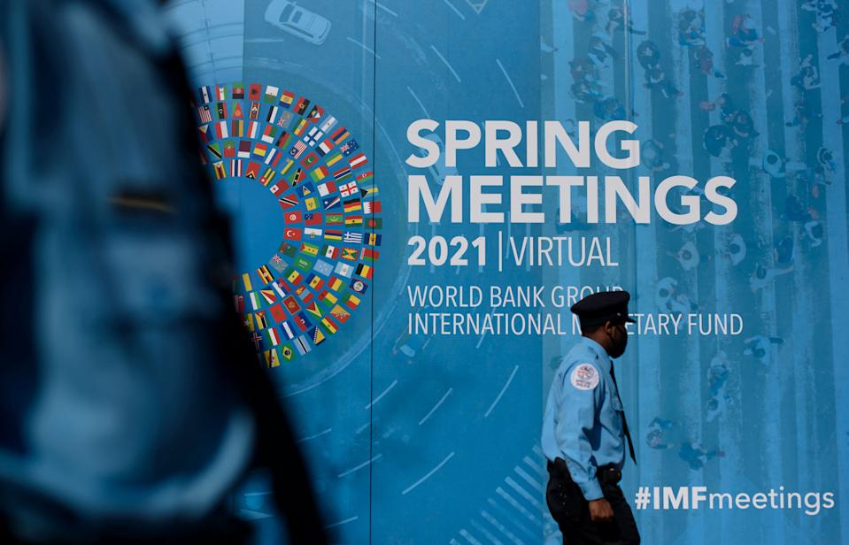 A security guards passes by a banner on an International Monetary Fund(IMF) headquarters building in Washington, DC on April 5, 2021. - The annual spring meetings of the International Monetary Fund (IMF) and the World Bank Group will be held virtually from April 5 to April 11, 2021. (Photo by MANDEL NGAN / AFP) (Photo by MANDEL NGAN/AFP via Getty Images)