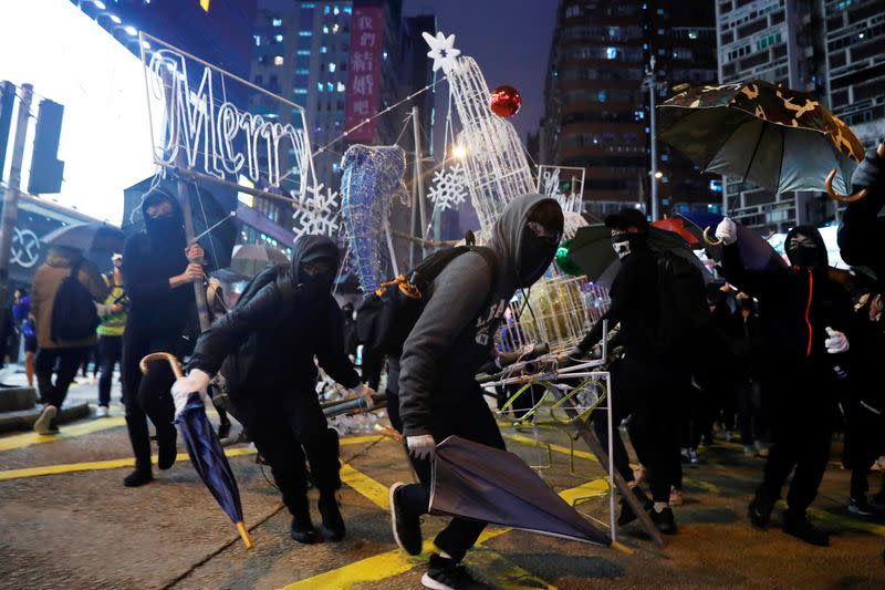 Anti-government protesters tear down Christmas and New Year's decorations during a demonstration on New Year's Eve outside Mong Kok police station in Hong Kong