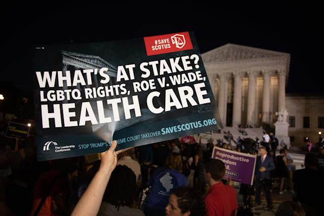 "<p>Hundreds assembled in front of the U.S. Supreme Court in Washington D.C., to protest Brett Kavanaugh, President Donald Trump's nominee to replace Justice Anthony Kennedy, on Monday night, July 9, 2018. ""What's at stake? LGBTQ Rights, Roe V. Wade, Health Care"" reads the sign. (Photo: Jeff Malet/Newscom via ZUMA Press) </p>"