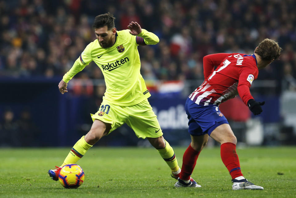 Barcelona's Lionel Messi drives the ball past Atletico's Antoine Griezmann, right, during a Spanish La Liga soccer match between Atletico Madrid and FC Barcelona at the Metropolitano stadium in Madrid, Saturday, Nov. 24, 2018. (AP Photo/Paul White)