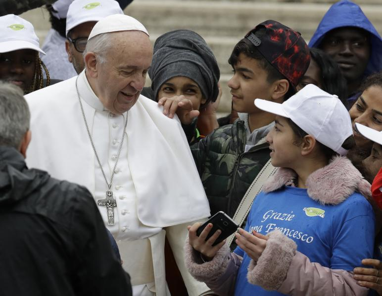 """Pope Francis meets a group of migrants recently arrived from Libya, wearing shirts with writing reading """"Thank you Pope Francis, at the end of his weekly general audience in St. Peter's Square, at the Vatican, Wednesday May 15, 2019. (AP Photo/Andrew Medichini)"""