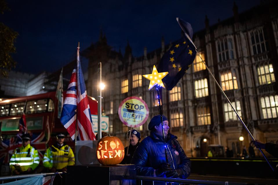 "LONDON, ENGLAND - OCTOBER 29: Anti-Brexit activists stand with a ""Stop Brexit"" halloween pumpkin outside the Houses of Parliament on October 29, 2019 in London, England. Later today, Prime Minister Boris Johnson will put forward a motion for a short bill proposing an early general election, which Labour Party leader Jeremy Corbyn says his party will support.  (Photo by Leon Neal/Getty Images)"