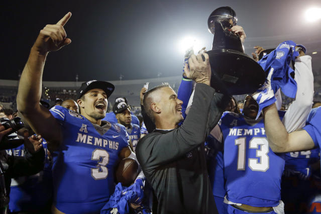 Memphis quarterback Brady White (3) celebrates as head coach Mike Norvell, center, lifts the trophy after they defeated Cincinnati in an NCAA college football game for the American Athletic Conference championship Saturday, Dec. 7, 2019, in Memphis, Tenn. (AP Photo/Mark Humphrey)