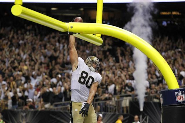 New Orleans Saints tight end Jimmy Graham (80) slam dunks over the goalpost after scoring on a touchdown reception in the second half of an NFL football game against the Arizona Cardinals in New Orleans, Sunday, Sept. 22, 2013. (AP Photo/Bill Haber)