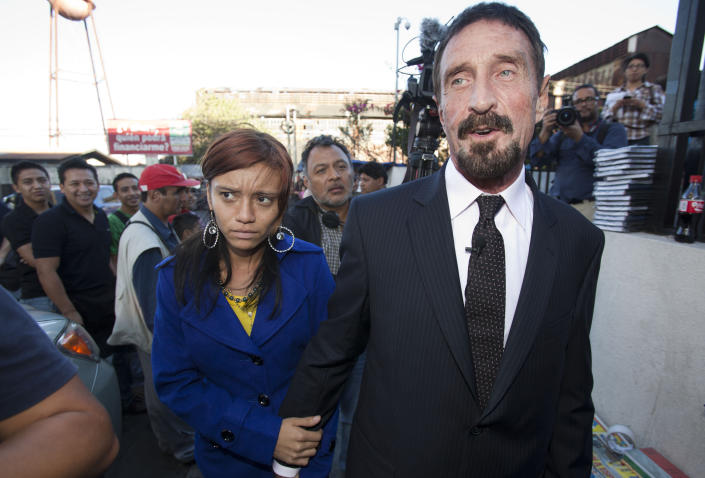 """Software company founder John McAfee, right, accompanied by his girlfriend """"Sam,"""" leaves after a press conference outside the Supreme Court in Guatemala City, Tuesday, Dec. 4, 2012. McAfee, 67, who has been identified as a """"person of interest"""" in the killing of his neighbor in Belize, 52-year-old Gregory Faull, has surfaced in public for the first time in weeks, saying Tuesday that he plans to ask for asylum in Guatemala because he fears persecution in Belize. (AP Photo/Moises Castillo)"""