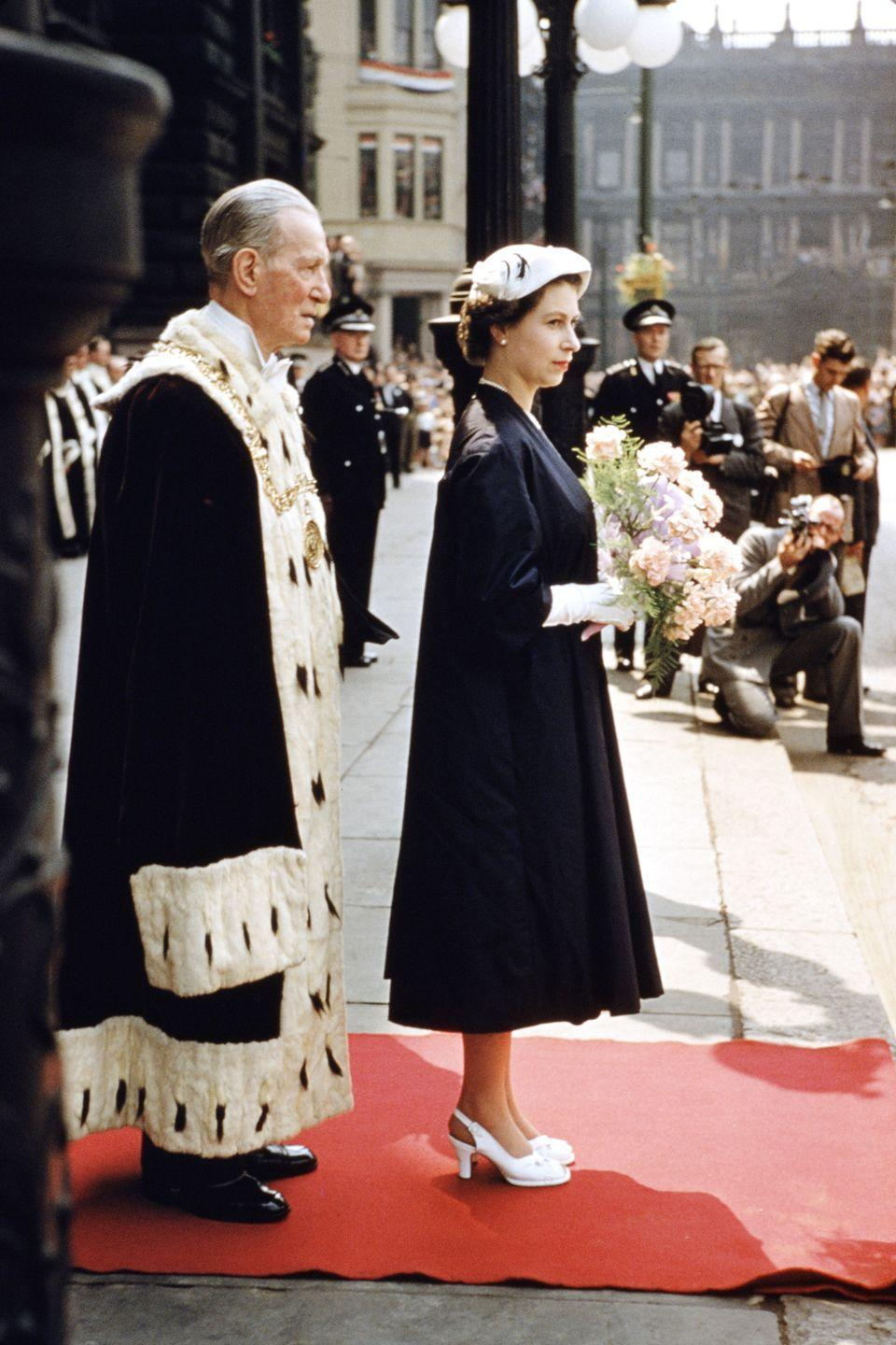 <p>In a blue A-line dress with white heels and gloves outside the City Chambers in Glasgow during a Coronation Tour of Scotland. Next to her is the Lord Provost of Glasgow, Thomas Kerr.</p>