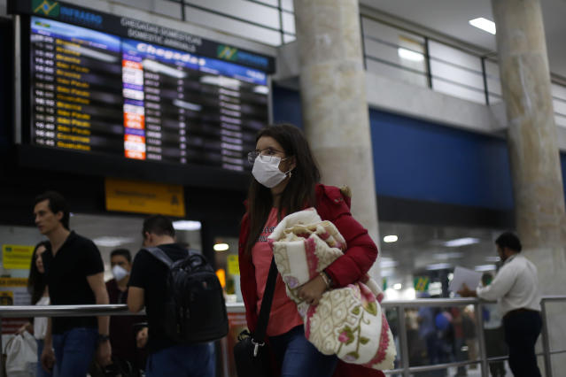 RIO DE JANEIRO, BRAZIL - MARCH 13: A passenger walks with a luggage wearing a protective mask at Santos Dumont Airport on March 13, 2020 in Rio de Janeiro, Brazil. According to the Ministry of Health, Brazil confirmed 98 cases of coronavirus (COVID-19). (Photo by Bruna Prado/Getty Images)