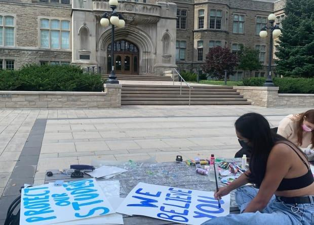 Third-year Western University student Paula Gomez, one of several organizers of a campus-wide walkout planned for Friday in London, Ont., creates posters on campus.  (Kate Dubinski/CBC News - image credit)