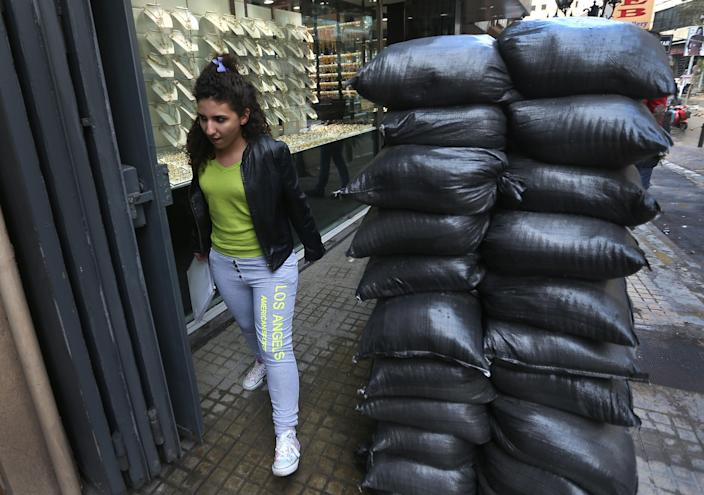 FILE - In this Tuesday, Jan. 28, 2014 photo, a Lebanese girl passes next to sand barriers that were set in front of jewelry shop, in a Shiite neighborhood in a southern suburb of Beirut, Lebanon. After a wave of car bomb attacks on Hezbollah's stronghold south of Beirut that left scores of people dead or wounded over the past three months, shop owners scared of more bombs have set up sand barriers in front of their institutions to reduce damage in case more blasts occur. The attacks that hit the south Beirut area known as Dahiyeh (suburb) has sacred many people in the area and increased security measures by Lebanese troops and members of the militant group.(AP Photo/Hussein Malla, File)