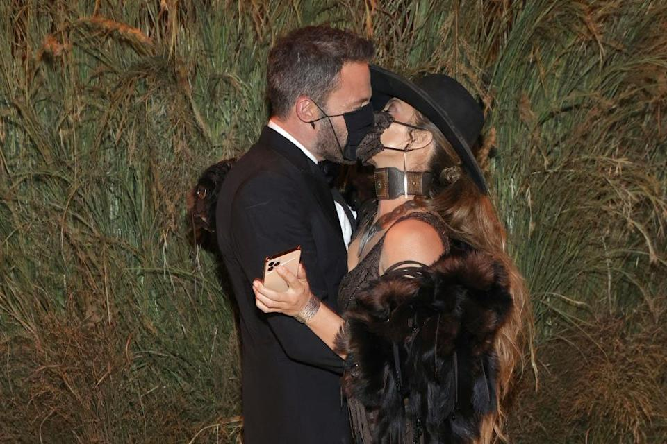 A close up ofBen Affleck and Jennifer Lopez kissing with face masks on