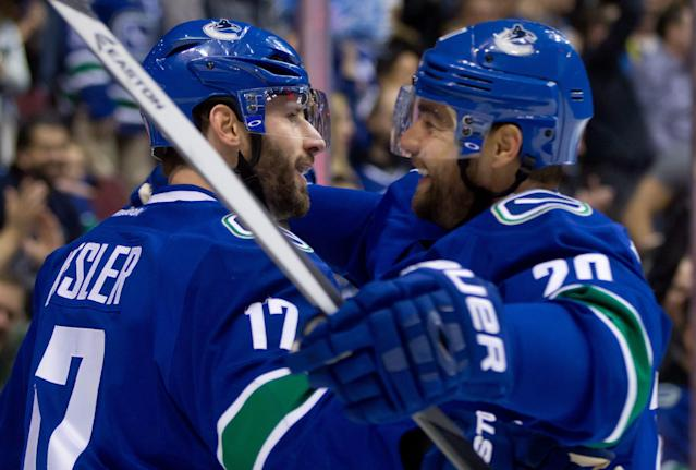 Vancouver Canucks' Ryan Kesler, left, and Chris Higgins celebrate Kesler's short-handed goal against the Minnesota Wild during the first period of an NHL hockey game Friday, Feb. 28, 2014, in Vancouver, British Columbia. (AP Photo/The Canadian Press, Darryl Dyck)