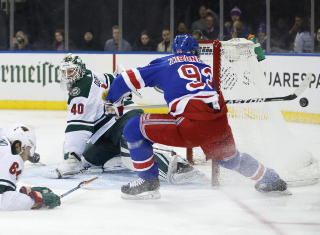 Minnesota Wild right wing Mikael Granlund (64) and New York Rangers center Mika Zibanejad (93), of Sweden, watches as the puck sails by Wild goaltender Devan Dubnyk (40) during the second period of an NHL hockey game in New York, Friday, Feb. 23, 2018. (AP Photo/Kathy Willens)